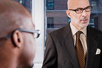 Close_up of two businessmen discussing in an office