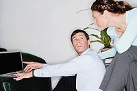 Businessman working on a laptop and looking at a businesswoman