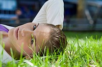Portrait of a businesswoman lying on grass in a park