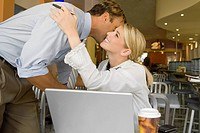 Businessman kissing a businesswoman in a restaurant