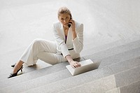 Businesswoman sitting on steps talking on a mobile phone and using a laptop
