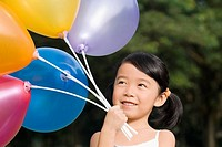 Close_up of a girl holding balloons