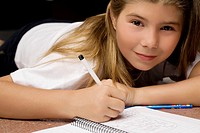 Portrait of a girl writing on a textbook with a pencil