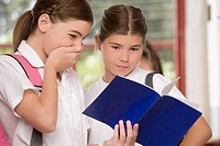 Close-up of a schoolgirl showing her textbook to another schoolgirl (thumbnail)