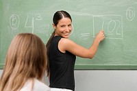 Female teacher teaching a schoolgirl in a classroom and smiling