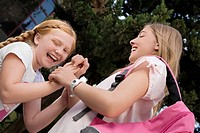 Low angle view of two schoolgirls playing clapping game and smiling (thumbnail)