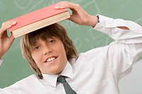 Portrait of a schoolboy holding a book over his head and smiling