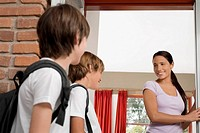 Female teacher looking at two schoolboys and smiling