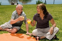 Senior couple holding glasses of juice at picnic