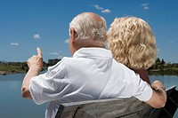 Rear view of a senior couple sitting on a bench at the lakeside