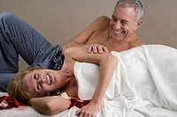 Mature woman with a senior man lying on a massage table and smiling