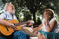 Senior man playing a guitar in front of a senior woman