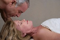 Close_up of a mature woman lying on a massage table with a senior man looking at her face
