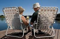 Rear view of a senior couple sitting on chairs at the lakeside (thumbnail)