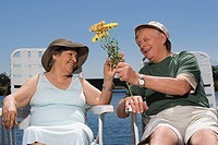 Senior man giving flowers to a senior woman and smiling