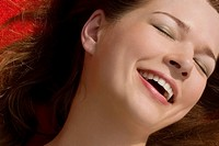 Close_up of a young woman smiling with her eyes closed