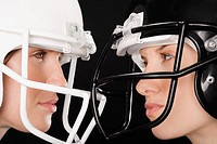 Close_up of two businesswomen wearing football helmets and looking at each other