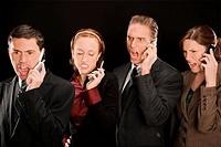 Four business executives talking on mobile phones