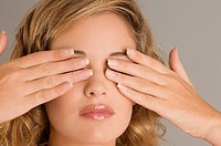 Close_up of a young woman covering her eyes with her hands
