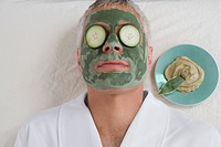 Close_up of a mature man lying down with a face pack and cucumber slices on her eyes