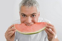 Portrait of a mature man eating a slice of watermelon
