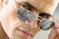 Close_up of a mid adult man peeking over his sunglasses