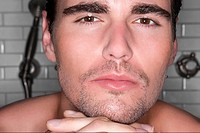Close_up of a young man with his hands on his chin and thinking
