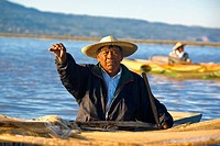Fisherman on a boat and showing a fish, Janitzio Island, Lake Patzcuaro, Patzcuaro, Michoacan State, Mexico