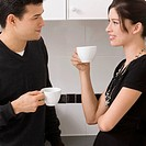 Young couple holding cups of tea and looking at each other