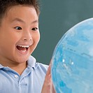 Close_up of a schoolboy looking at a globe and laughing