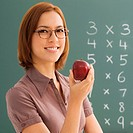 Portrait of a female teacher holding an apple and smiling