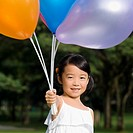 Portrait of a girl holding balloons and smiling