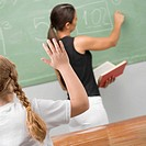 Rear view of a schoolgirl in a classroom with her hand raised