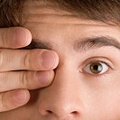 Close-up of a young man covering his one eye (thumbnail)
