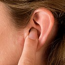 Close_up of a young woman's finger in her ear