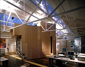 Modern office in old factory with metal roof trusses and shuttering plywood intervention. Architect: Pierre D'Avoine