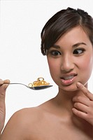 Close_up of a young woman holding a spoon of pills