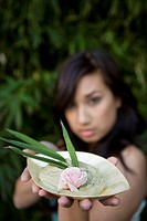 Close_up of a young woman holding a bowl of herb