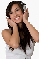 Portrait of a young woman listening to music with headphones and smiling