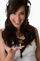 Portrait of a young woman listening to music with headphones and laughing