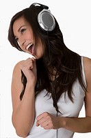 Close_up of a young woman listening to music with headphones and laughing