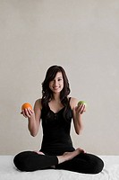 Portrait of a young woman sitting in a yoga position and holding an orange and an avocado in her both hands