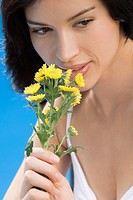 Close_up of a young woman smelling flowers