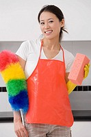 Portrait of a young woman holding a bath sponge and a feather duster