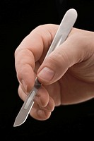 Close-up of a doctor's hand holding a scalpel (thumbnail)