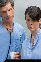Male surgeon and a female surgeon looking at a medical record (thumbnail)