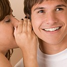 Side profile of a young woman whispering to a young man