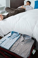 Shirts in a suitcase and a businessman sleeping on the bed