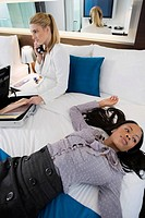 Businesswoman talking on a cordless phone and another businesswoman lying on the bed