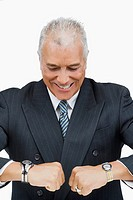 Close_up of a businessman looking at his wristwatches